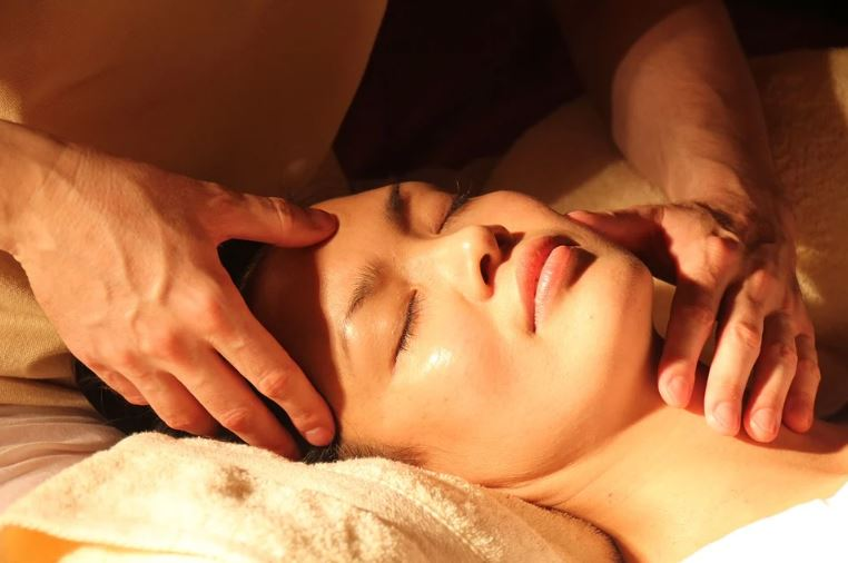 woman lying down while receiving a facial treatment massage