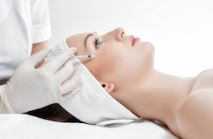 woman lying down and receiving a restylane skinbooster filler injection by an aesthetic professional